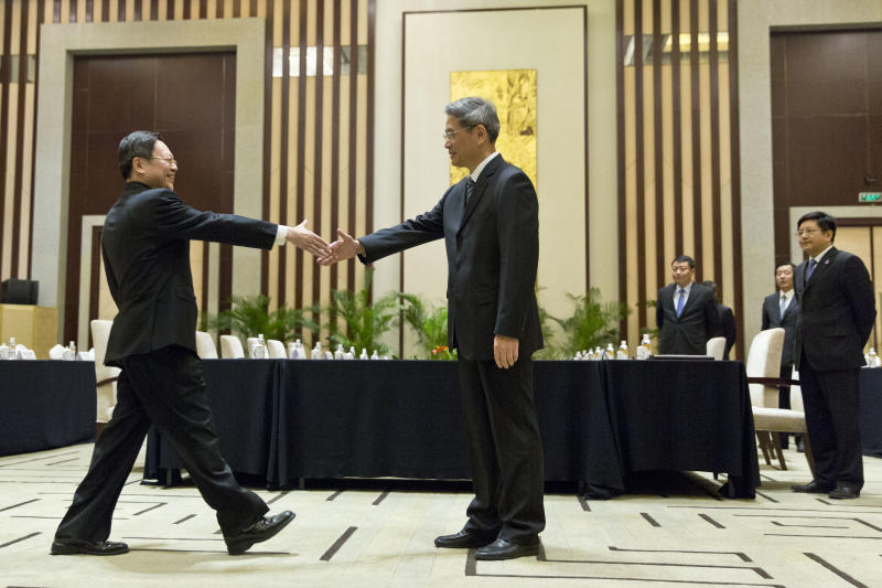 Wang Yu-chi, head of Taiwan's Mainland Affairs Council, left, shakes hands with Zhang Zhijun, director of China's Taiwan Affairs Office, right, before their meeting in Nanjing, in eastern China's Jiangsu Province, Tuesday, Feb. 11, 2014. Taiwan and China are holding their highest-level talks since splitting amid a civil war 65 years ago, hoping to further boost contacts and ease lingering tensions, even as political developments on the self-governing island swing away from Beijing's goal of eventual unification. (AP Photo/Alexander F. Yuan)
