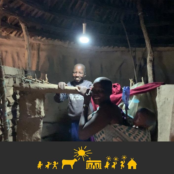 A rural African family lights up their home at night using the same battery charged by the Solar Cow.