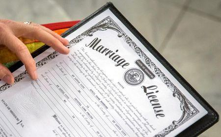 Reverend Katie Hotze-Wilton signs a marriage license at a same-sex wedding ceremony at City Hall in St. Louis, Missouri November 5, 2014. REUTERS/Whitney Curtis