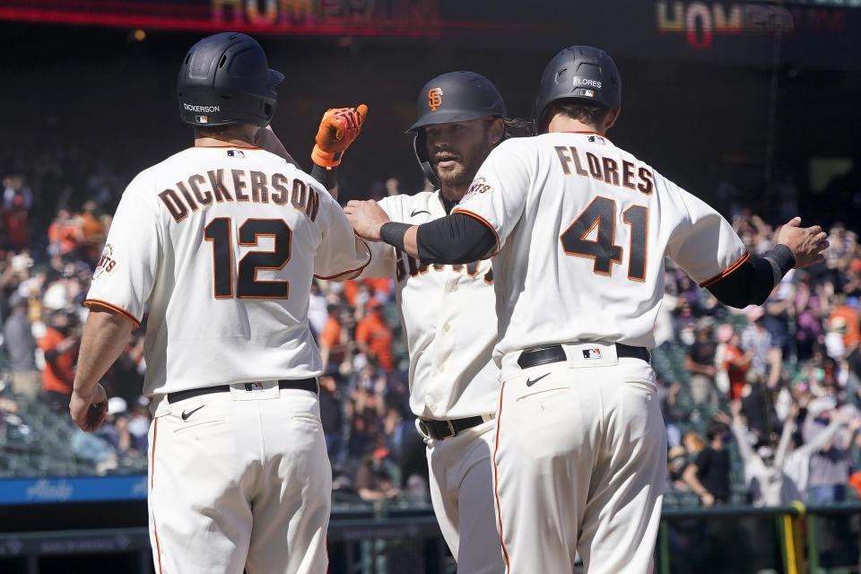 San Francisco Giants' Brandon Crawford, center, celebrates after a three-run home run that also scored Alex Dickerson (12) and Wilmer Flores (41) during the sixth inning of a baseball game against the Colorado Rockies in San Francisco, Saturday, April 10, 2021. (AP Photo/Jeff Chiu)