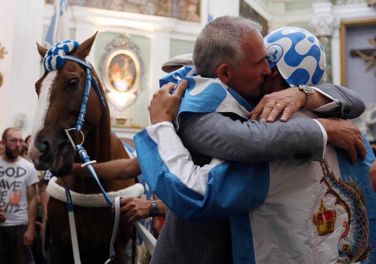 "Captain of the ""Onda"" (Wave) parish Alessandro Toscano embraces jockey Giovanni Atzeni at the church before the Palio horse race in Siena, Italy July 2, 2017. REUTERS/Stefano Rellandini"