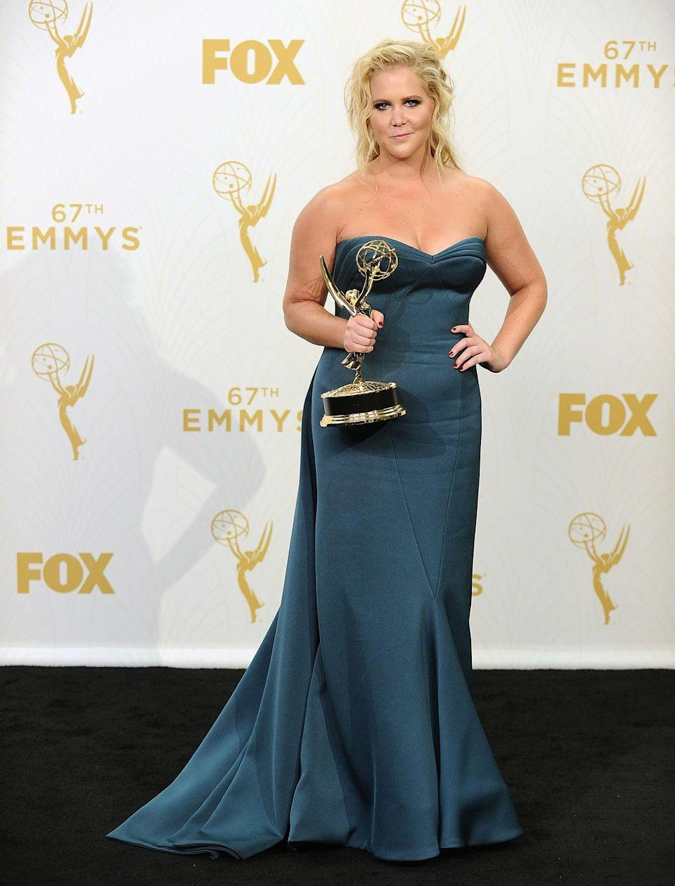 """<p>Schumer wore this dark teal dress when she won an Emmy in 2015 for Outstanding Variety Sketch Series for <em>Inside Amy Schumer</em><span class=""""redactor-invisible-space"""">.</span></p>"""