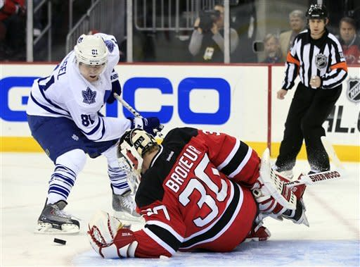 Toronto Maple Leafs' Phil Kessel (81) tries to slap the puck past New Jersey Devils goalie Martin Brodeur during the first period of an NHL hockey game in Newark, N.J., Friday, March 23, 2012. (AP Photo/Mel Evans)