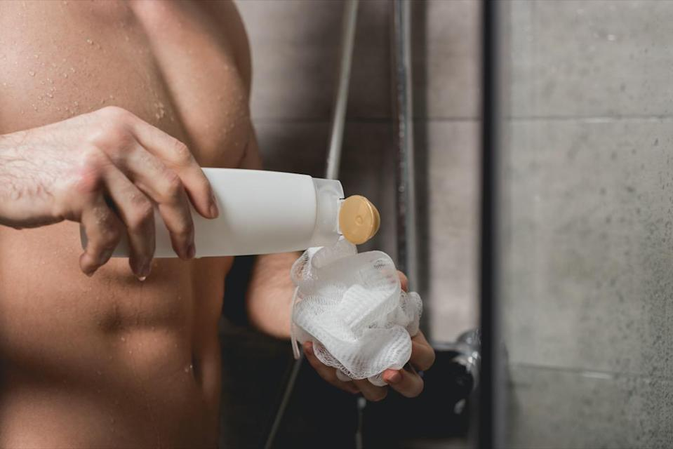partial view of man holding loofah and shower gel