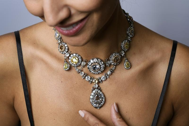 A model poses with a parure of antique coloured diamond jewels once owned by Russian empress Catherine I, during a press preview by Sotheby's auction house on November 9, 2016 in Geneva (AFP Photo/Fabrice Coffrini)