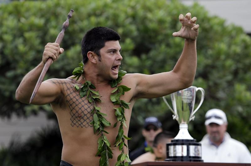 Traditional Hawaiian dancer Kamalu Elaban dances in view of the championship trophy during an opening ceremony at the Tournament of Champions golf tournament, Friday, Jan. 4, 2013, in Kapalua, Hawaii. (AP Photo/Elaine Thompson)