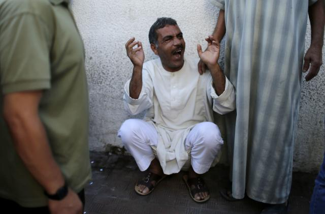 A relative of three Palestinian children from the Al-Rifi family, who medics said were killed in an Israeli air strike, reacts outside a hospital morgue in Gaza City August 21, 2014. Israel killed three senior Hamas commanders in an air strike on the Gaza Strip on Thursday, the clearest signal yet that Israel is intent on eliminating the group's military leadership after a failed attempt on the life of its top commander this week. As well as the Hamas commanders killed, Palestinian medics reported 19 other deaths on Thursday, including three children. REUTERS/Suhaib Salem (GAZA - Tags: POLITICS CIVIL UNREST MILITARY CONFLICT)