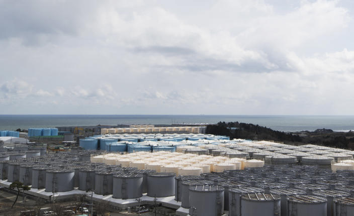 This photo shows tanks (in gray, beige and blue) storing water that was treated but still radioactive after it was used to cool down spent fuel at the Fukushima Daiichi nuclear power plant in Okuma town, Fukushima prefecture, northeastern Japan, Saturday, Feb. 27, 2021. (AP Photo/Hiro Komae)