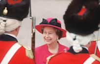 <p>Bold color statements all around—courtesy of these red military uniforms from the American Revolution and the Queen's hot pink style—during the Queen's trip to Wales in 1989.</p>