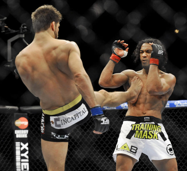 Josh Thomson, left, kicks Benson Henderson, right, during the main event of the UFC mixed martial arts event in Chicago, Saturday, Jan., 25, 2014. (AP Photo/Paul Beaty)