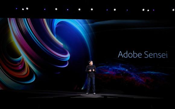 A man on a darkened stage with a colorful background with the words Adobe's Sensei, the company's AI system.