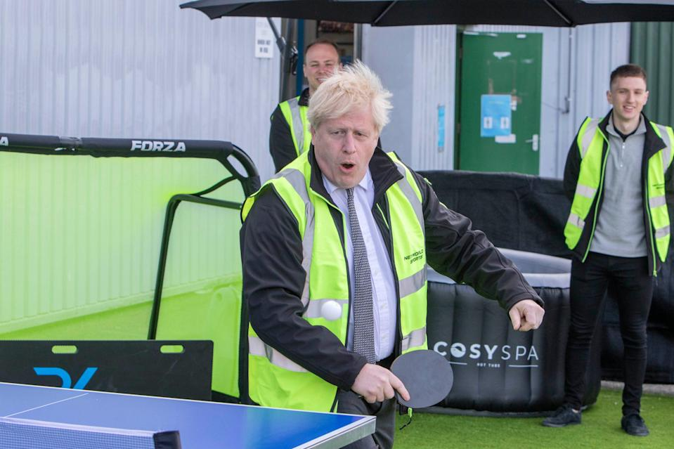 <p>Boris Johnson playing table tennis during a visit to Next World Sports in Wrexham on Monday</p> (PA)