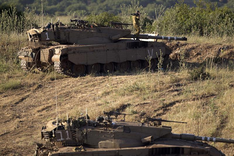 "An Israeli soldier works on top of a tank in a position in the Israeli controlled Golan Heights, on the border with Syria, Tuesday, May 21, 2013. Israel's military chief has issued a stern warning to Syrian leader Bashar Assad after an Israeli military jeep came under fire from Syrian forces early Tuesday. Lt. Gen. Benny Gantz said on Tuesday that Israel will not allow the Golan Heights ""to become a comfortable sphere for Assad to operate from."" He said that if the situation deteriorates further, Assad ""will have to bear the consequences."" (AP Photo/Ariel Schalit)"