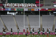 Players from Ireland and South Africa shake hands as they leave the pitch after their men's rugby sevens match at the 2020 Summer Olympics, Monday, July 26, 2021 in Tokyo, Japan. (AP Photo/Shuji Kajiyama)