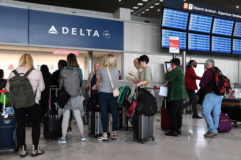 Travellers queue at a Delta Airlines desk at Paris-Charles-de-Gaulle airport after a US 30-day ban on travel from Europe due to the COVID-19 spread in Roissy-en-France on March 12, 2020. - US President Donald Trump announced on March 11, 2020 a shock 30-day ban on travel from mainland Europe over the coronavirus pandemic that has sparked unprecedented lockdowns, widespread panic and another financial market meltdown. (Photo by Bertrand GUAY / AFP) (Photo by BERTRAND GUAY/AFP via Getty Images)