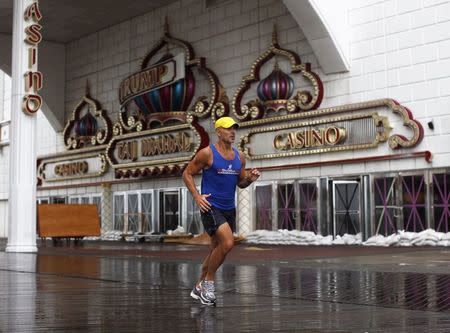 A jogger runs past the sandbagged and closed Trump Taj Mahal Casino on the boardwalk at Atlantic City, New Jersey in this file photo from August 27, 2011. REUTERS/Jason Reed/Files