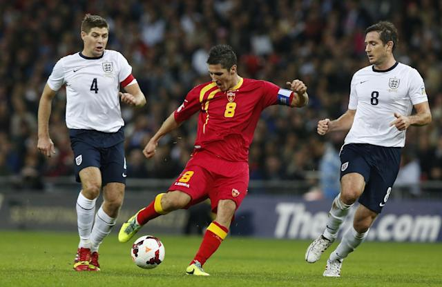 Montenegro's Stevan Jovetic, centre takes a shot on goal watched by England's Steven Gerrard, left and teammate Frank Lampard during the World Cup Group H qualification soccer match between England and Montenegro at Wembley stadium in London, Friday, Oct. 11, 2013 . (AP Photo/Sang Tan)