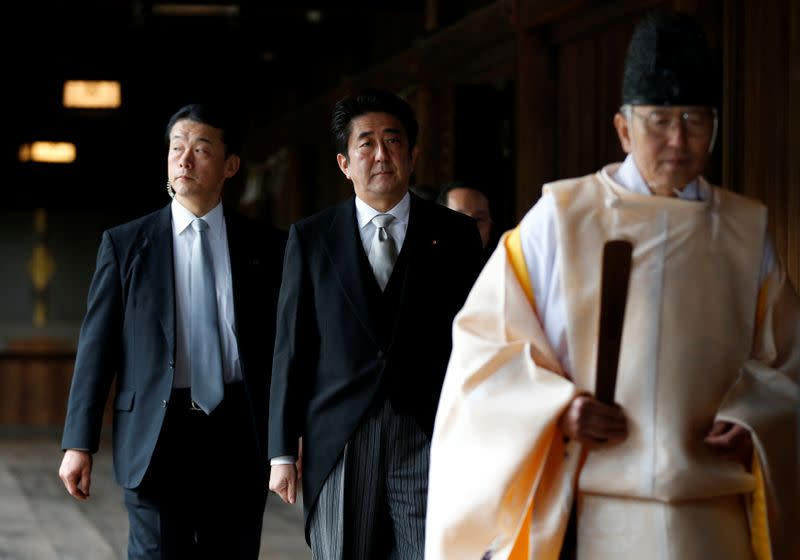 FILE PHOTO : Japan's PM Abe is led by a Shinto priest as he visits Yasukuni shrine in Tokyo