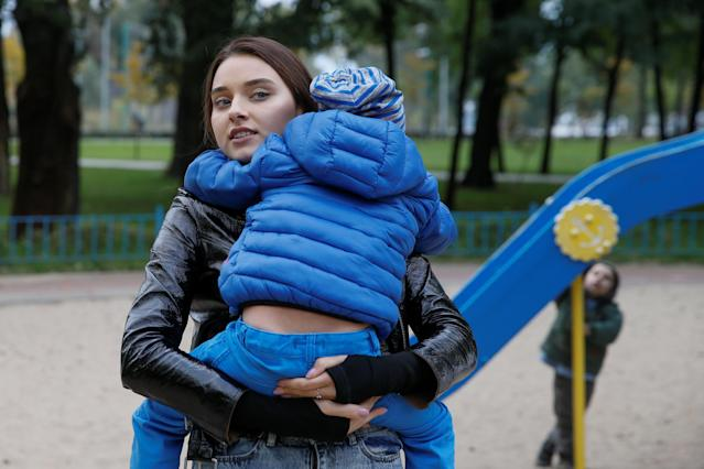Veronika Didusenko, who was stripped of her Miss Ukraine 2018 title after the organizers discovered the model was divorced and has a child, holds her 4-year-old son before a 2018 interview with Reuters in Kiev, Ukraine. (Reuters/Valentyn Ogirenko)