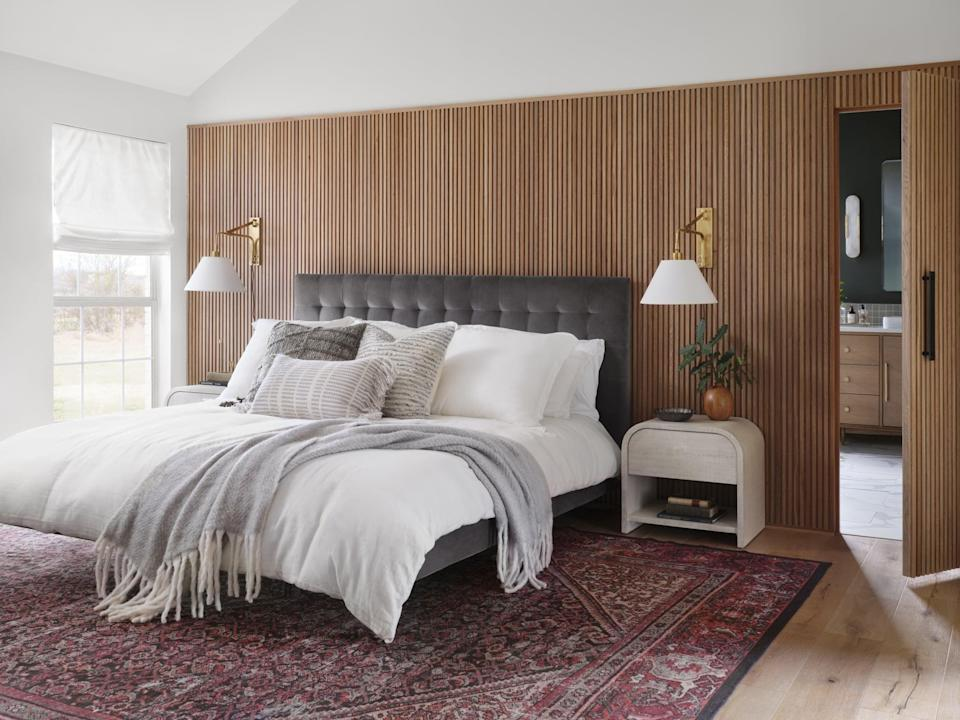 <p>To create warmth and dimension, Chip and Joanna covered the back wall with vertical white oak slats and mounted sconces on each side of the bed.</p>