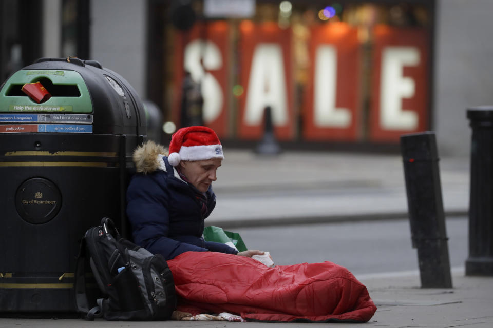 A homeless man wears a santa hat as he sits on Oxford Street in London, Saturday, Dec. 26, 2020. London is currently in Tier 4 with all non essential retail closed and people have been asked to stay at home, on what is usually one of the busiest retail days of the year with the traditional Boxing Day sales in shops. (AP Photo/Kirsty Wigglesworth)
