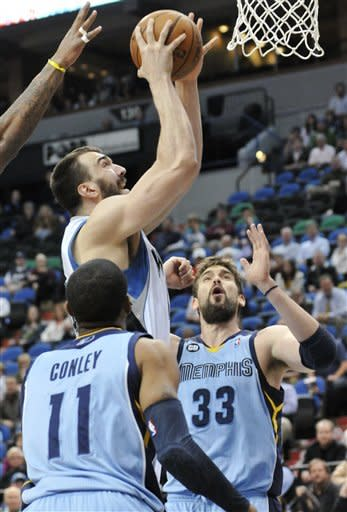 Minnesota Timberwolves' Nikola Pekovic, of Montenegro, lays up a shot between Memphis Grizzlies' Mike Conley, left, and Marc Gasol, of Spain, during the first half of an NBA basketball game Tuesday, April 17, 2012, in Minneapolis. (AP Photo/Jim Mone)