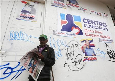 A citizen reads a newspaper in front of a campaign house of presidential candidate Oscar Zuluaga of the Centro Democratico party in Soacha