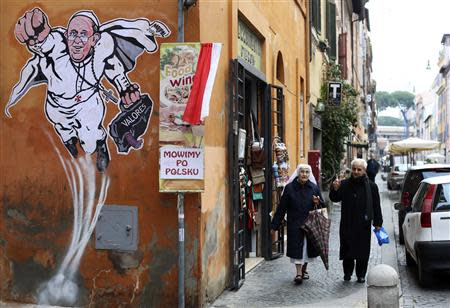 A priest and a nun walk by a large drawing of Pope Francis depicting him as a superhero on a wall near the Vatican January 29, 2014. REUTERS/Alessandro Bianchi