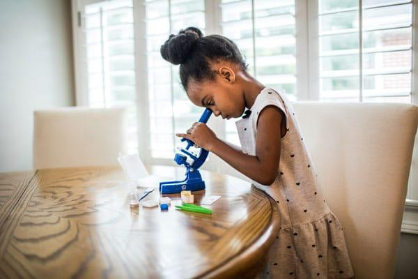 Young girl looking in microscope