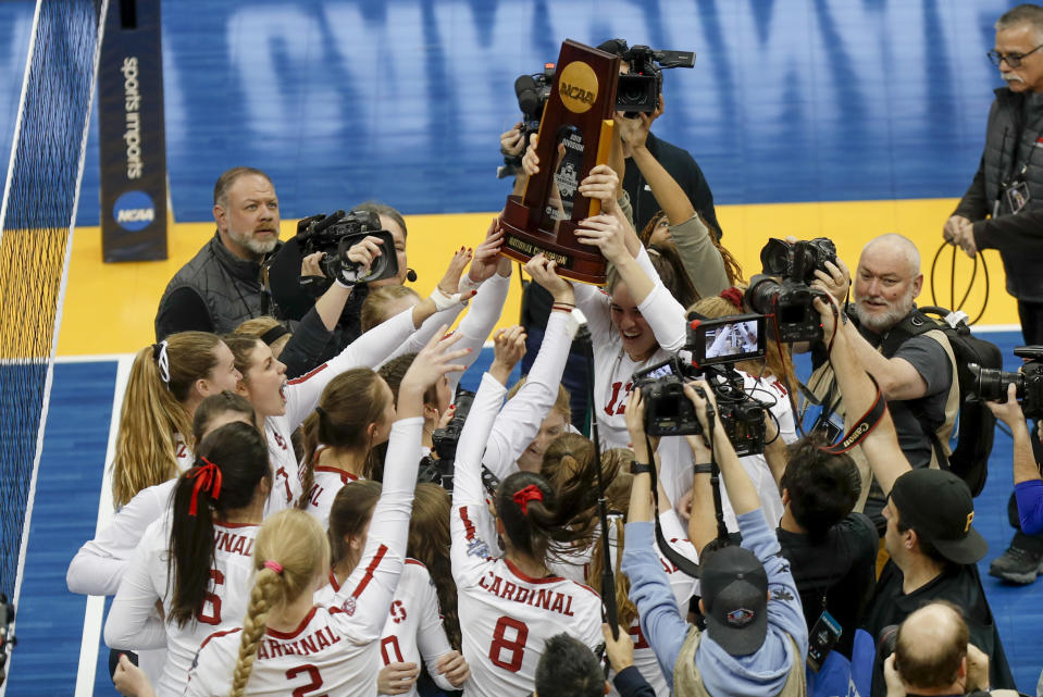 FILE - The Stanford women's volleyball team holds the championship trophy overhead after defeating Wisconsin for the NCAA Division I women's volleyball championship, in Pittsburgh, in this Saturday, Dec. 21, 2019, file photo. Women's volleyball will be the first of the NCAA fall sports to play this spring after the COVID-19 pandemic prompted most conferences to cancel or shorten their 2020 fall seasons and the NCAA to call off the national tournament. (AP Photo/Keith Srakocic, File)