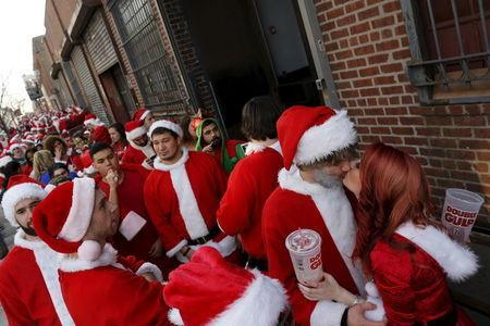 Revelers dressed in Santa Claus and other holiday themed outfits take part in the annual SataCon event in the Brooklyn borough of New York, December 12, 2015. REUTERS/Brendan McDermid