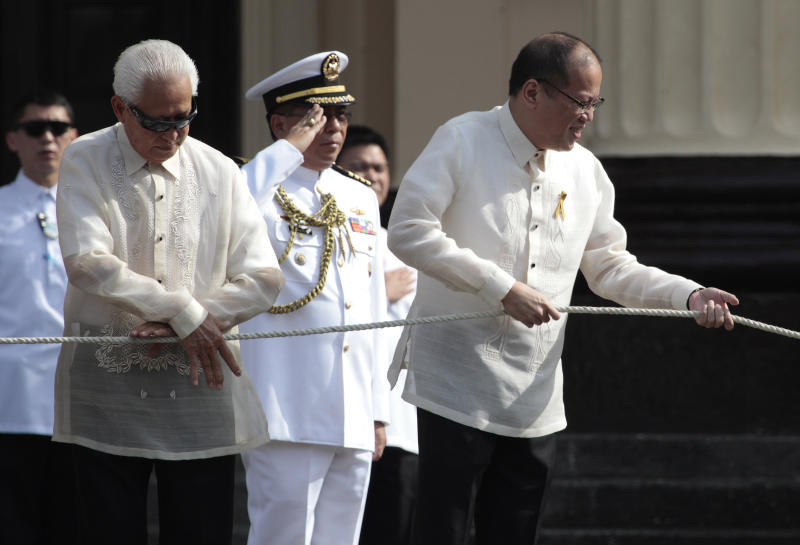 Philippine President Benigno Aquino III, right, leads flag raising ceremonies to mark the 115th Philippine Independence Day at Liwasang Bonifacio, a square named after Filipino revolutionary leader Andres Bonifacio, in Manila, Philippines on Wednesday June 12, 2013. Aquino vowed Wednesday his country will not back down from any challenge to its sovereignty and territory amid a sea dispute with China. (AP Photo/Aaron Favila)