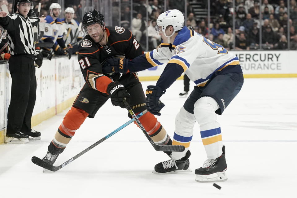Anaheim Ducks right wing David Backes, left, passes around St. Louis Blues defenseman Colton Parayko during the second period of an NHL hockey game in Anaheim, Calif., Wednesday, March 11, 2020. (AP Photo/Chris Carlson)