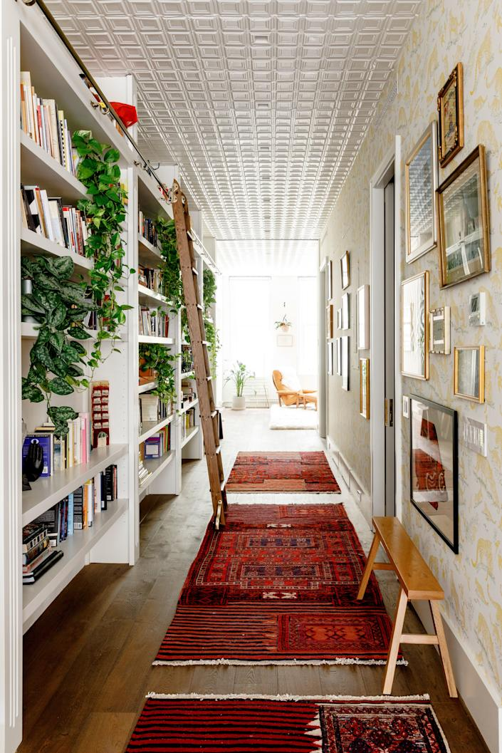 """The entry hallway of Stranger Things actor David Harbour's NYC loft features vintage oriental rugs sourced from Hasan's Rugs and """"Tendresse Feline"""" wallpaper from Hermès. A gallery wall of photos gives the space a more vintage feel."""