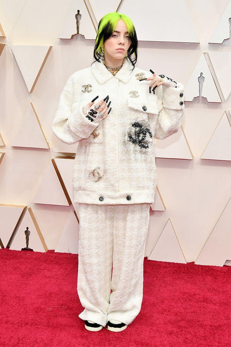 """<p>At the <a href=""""https://www.cosmopolitan.com/uk/beauty-hair/celebrity-hair-makeup/a30840804/billie-eilish-oscars-hair-igk-next-level-spray/"""" rel=""""nofollow noopener"""" target=""""_blank"""" data-ylk=""""slk:Oscars"""" class=""""link rapid-noclick-resp"""">Oscars</a>, Billie updated her grandma-chic Chanel suit with a graffiti-effect logo, her trademark gothic nails, and skate sneakers.</p>"""