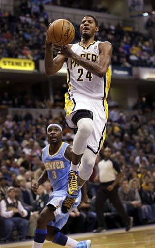 Indiana Pacers forward Paul George, right, goes to the basket in front of Denver Nuggets guard Ty Lawson during the second half of an NBA basketball game in Indianapolis, Friday, Dec. 7, 2012. The Nuggets won 92-89. (AP Photo/AJ Mast)