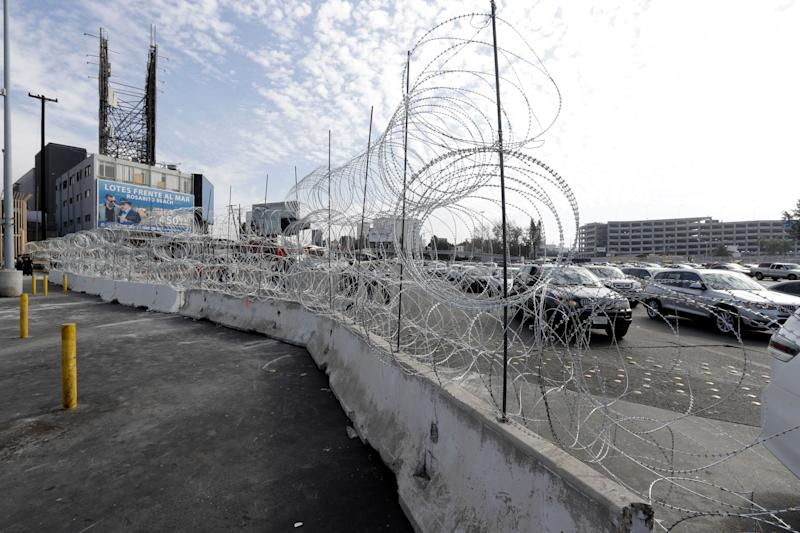 Cars lined up to cross into the United States from Tijuana, Mexico, are seen through barriers topped with concertina wire at the San Ysidro port of entry. Thieves have been taking the wire and selling it in Tijuana for home security. (Photo: Gregory Bull/ASSOCIATED PRESS)