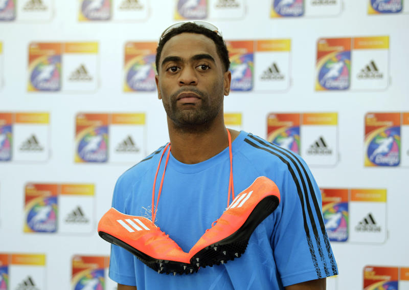 FILe - In this Aug. 25, 2011 file photo, U.S. sprinter Tyson Gay wears Adidas footwear around his neck while posing for photographers after speaking at a news conference for the World Athletics Championships in Daegu, South Korea. Adidas has suspended its sponsorship of Gay after the American sprinter's positive doping test. (AP Photo/Matt Dunham, File)