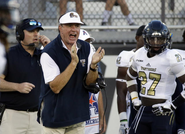 Florida International coach Butch Davis, front left, encourages his players during the first half of an NCAA college football game against Central Florida, Thursday, Aug. 31, 2017, in Orlando, Fla. (AP Photo/John Raoux)