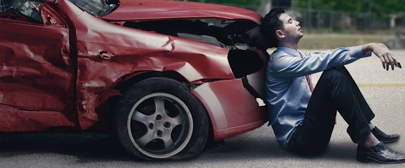 Frustrated man sitting on the ground leaning back on his wrecked car