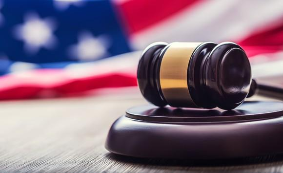 Gavel resting on a wooden stand in front of a large U.S. flag.