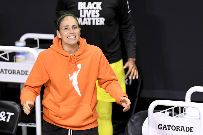 Sue Bird in the famous orange WNBA logo hoodie on the sidelines.
