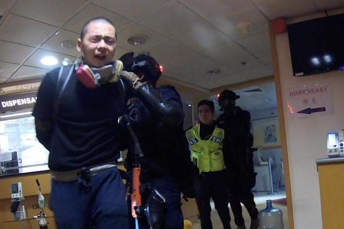 Riot police detain a protester and a medic during pre-dawn police operations at Hong Kong Polytechnic University