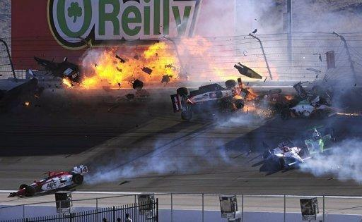 The car of Dan Wheldon (top L) bursts into flames in a 15 car pile up during the Las Vegas Indy 300. Wheldon was seriously hurt in a massive 15-car crash that sent several cars airborne early in the Las Vegas 300 IndyCar series finale