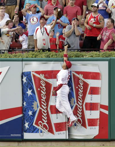 St. Louis Cardinals center fielder Jon Jay leaps at the wall as a fan catches a home run ball hit by Chicago Cubs' Welington Castillo in the third inning of a baseball game on Thursday, June 20, 2013 in St. Louis.(AP Photo/Tom Gannam)