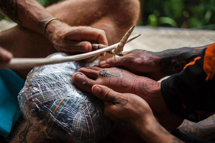 """A tattoo artist uses the traditional """"hand tapping"""" method during a tattoo festival in the village of Maguwoharjo located in Yogyakarta (AFP Photo/Suryo Wibowo)"""