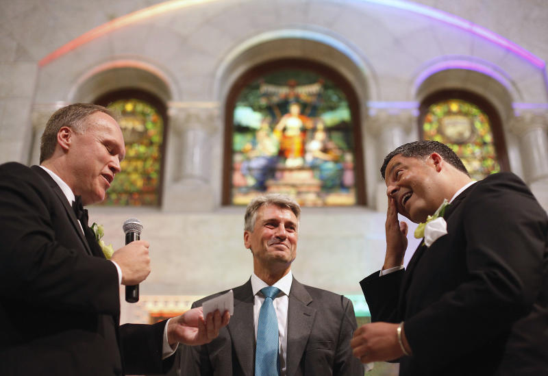 """FILE - In this Aug. 1, 2013 file photo, Minneapolis Mayor R.T. Rybak, center, officiates at the wedding of Al Giraud, right, and his partner Jeff Isaacson at the Minneapolis City Hall. They were the first gay couple legally married in Minnesota. Rybak is hitting the road to promote his state's new gay marriage law. He is traveling to Chicago on Thursday, Sept. 5 to launch a """"Marry in Minneapolis"""" campaign in the hopes that Illinois gay and lesbian couples will do just that. Illinois has not passed a gay marriage law, an issue scheduled to come before state lawmakers again this fall. (AP Photo/Stacy Bengs, File)"""