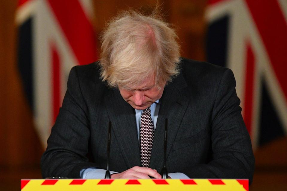 Boris Johnson looks down at the podium during a media briefing after the UK recorded 100,000 coronavirus deathsPA