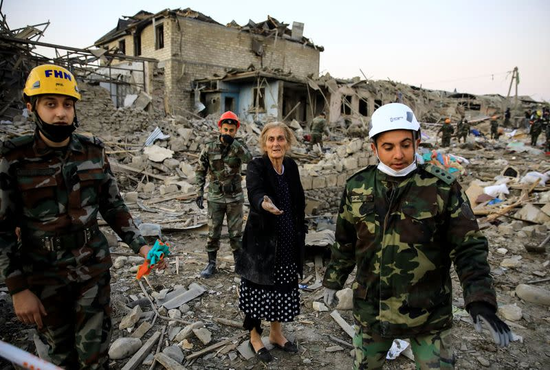 A woman reacts while standing on the ruins of her home as search and rescue teams work on a blast site hit by a rocket in the city of Ganja