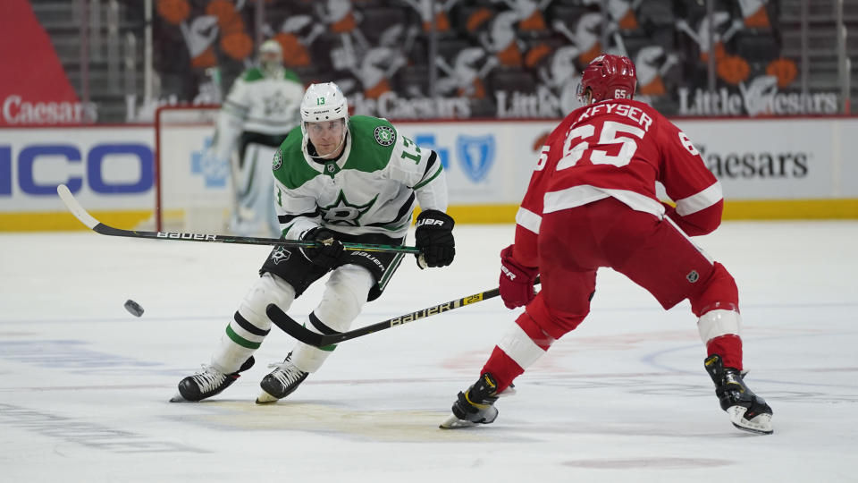 Dallas Stars' Mark Pysyk (13) flips the puck past Detroit Red Wings defenseman Danny DeKeyser (65) in the first period of an NHL hockey game Thursday, April 22, 2021, in Detroit. (AP Photo/Paul Sancya)